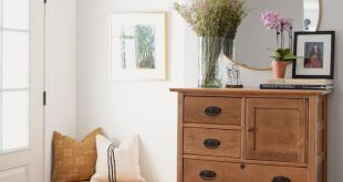 Entry way with a wood dresser for storage and a bench for shoes