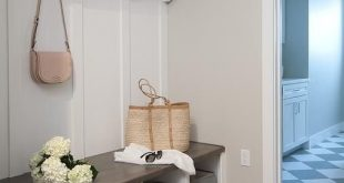 Oak wood floors accent gray walls highlighting a white built in bench fitted wit...