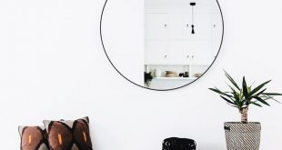 entryway // circle mirror // wooden bench // potted plant // decorative pillows ...